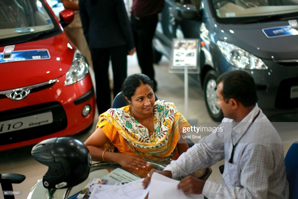 Locals at a car dealership , on April 14, 2008 in Bangalore, India. Many residents work for multi-national cooperations and the economy is booming. New construction for offices is under way. Shopping malls open frequently and the shops are full of western merchandise for workers with high disposable income. India's new middle class is about 300 million, and growing.