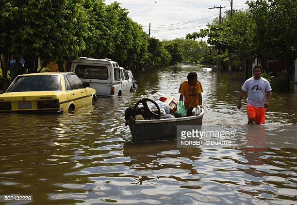 Locals attempt to recover belongings at a flooded neighbourhood in Asuncion on December 24 2015 Constant and heavy rains in the country have caused...