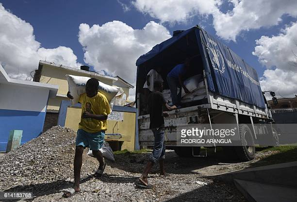 Locals carry aid from the UN's World Food Programme in Port Salut southwest of PortauPrince on October 12 following the passage of Hurricane Matthew...