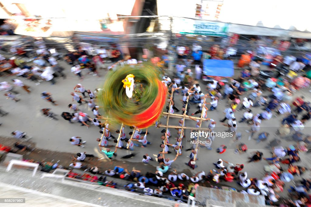 Locals carry as well as rotates top part of a chariot of Lord Narayan across the streets of Hadigaun during Lord Narayan jatra festival in Hadigaun, Kathmandu, Nepal on Friday, October 06, 2017. Once in a every year right after Dashain Festival this festival celebrates. The Narayan Jatra Festival of Hadigaun is a unique Festival in the capital involving three circular bamboo structures, above which an idol of the Lord Narayan in placed, and then rotated by two people standing below.