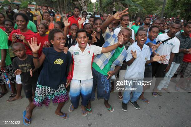 Locals cheer as Prince William Duke of Cambridge and Catherine Duchess of Cambridge travel in a special boat vehicle to Honiara Cathederal during...