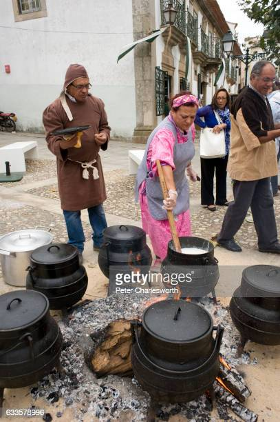 Locals cook soup and stews in large castiron pots over an open fire at a local 'medieval' festival in the small rural town of Coja where locals get...