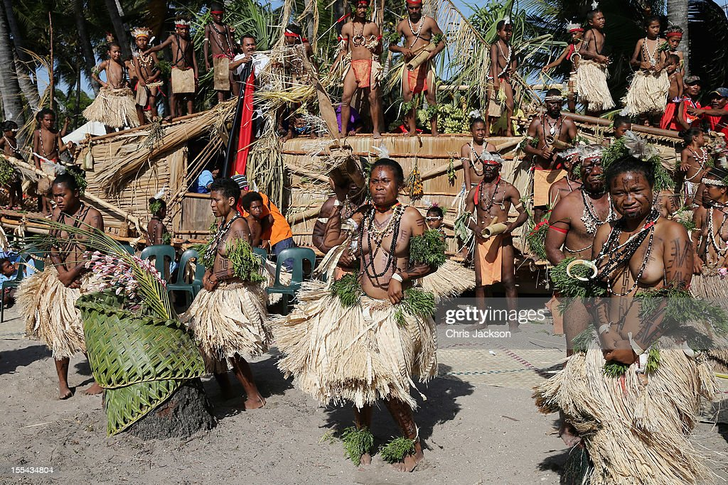 Locals dance on a specially constructed 'boat' as they greet Camilla Duchess of Cornwall and Prince Charles Prince of Wales during a visit to Borea...