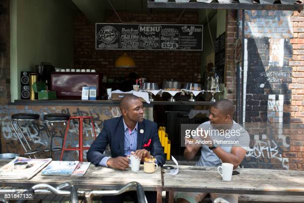 Locals drink coffee in a corner coffee shop in Maboneng district on March 15 2016 in downtown Johannesburg South Africa A former derelict industrial...
