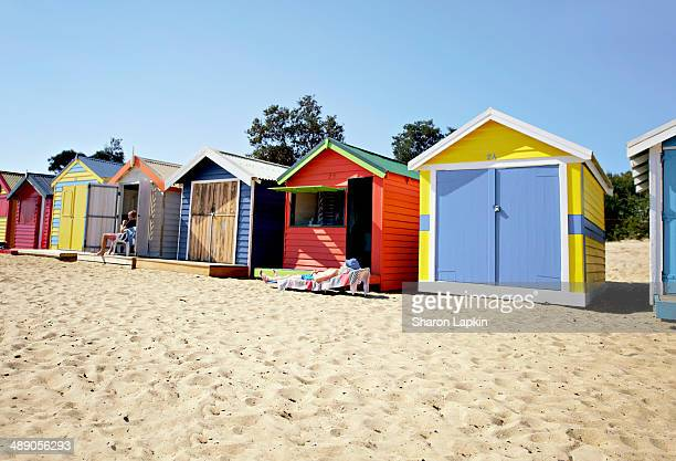Locals enjoying the sun outside beach huts at Brighton in Australia