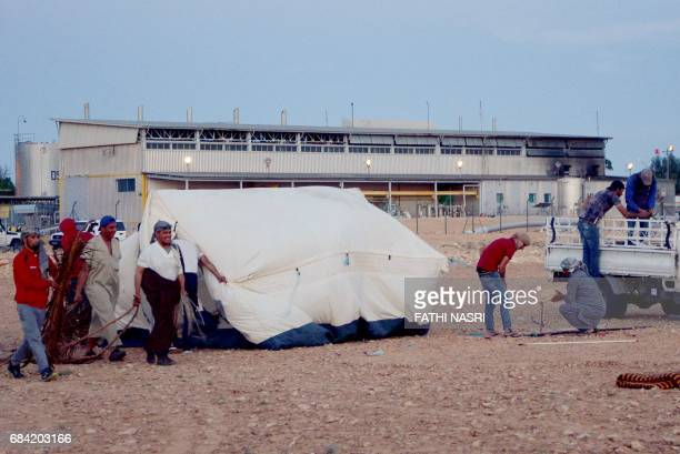 Locals erect a tent as they stage a sitin outside elKamour petroleum pumping station in Tunisia's southern state of Tatatouine on May 16 2017 Since...