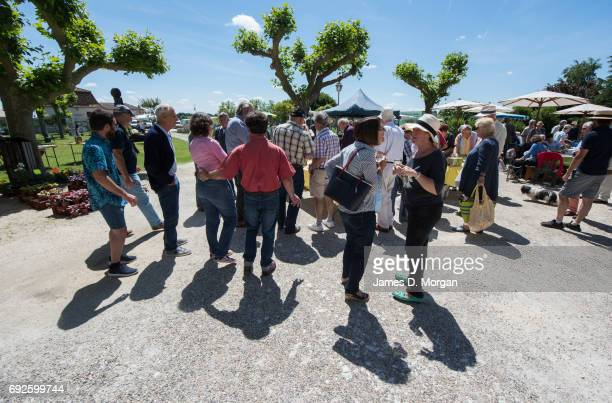 locals gather for wine underneath the lime trees at a local fair on June 5 2017 in Saussignac France Monday is a public holiday in France to celbrate...