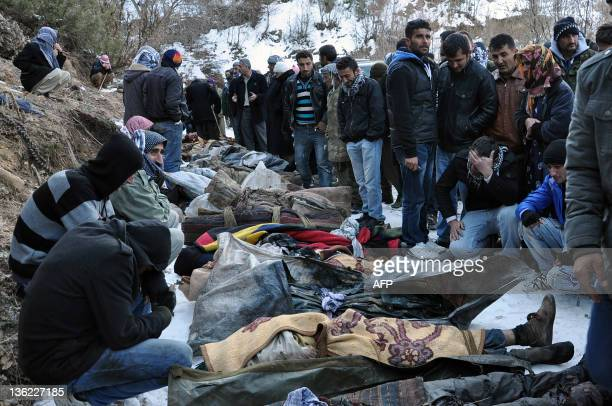 Locals gather in front of the bodies of people who were killed in a warplane attack in the Ortasu village of Uludere in the Sirnak province on...