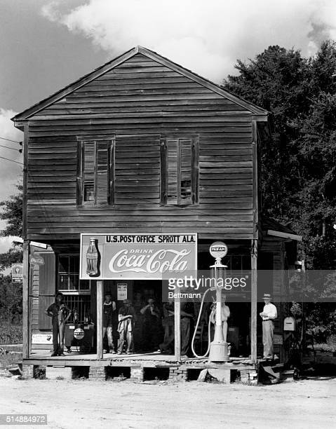 Locals gather on the porch of the Southern Cross Road Grocery Store which serves also as gasoline station and post office for the town of Sprott...