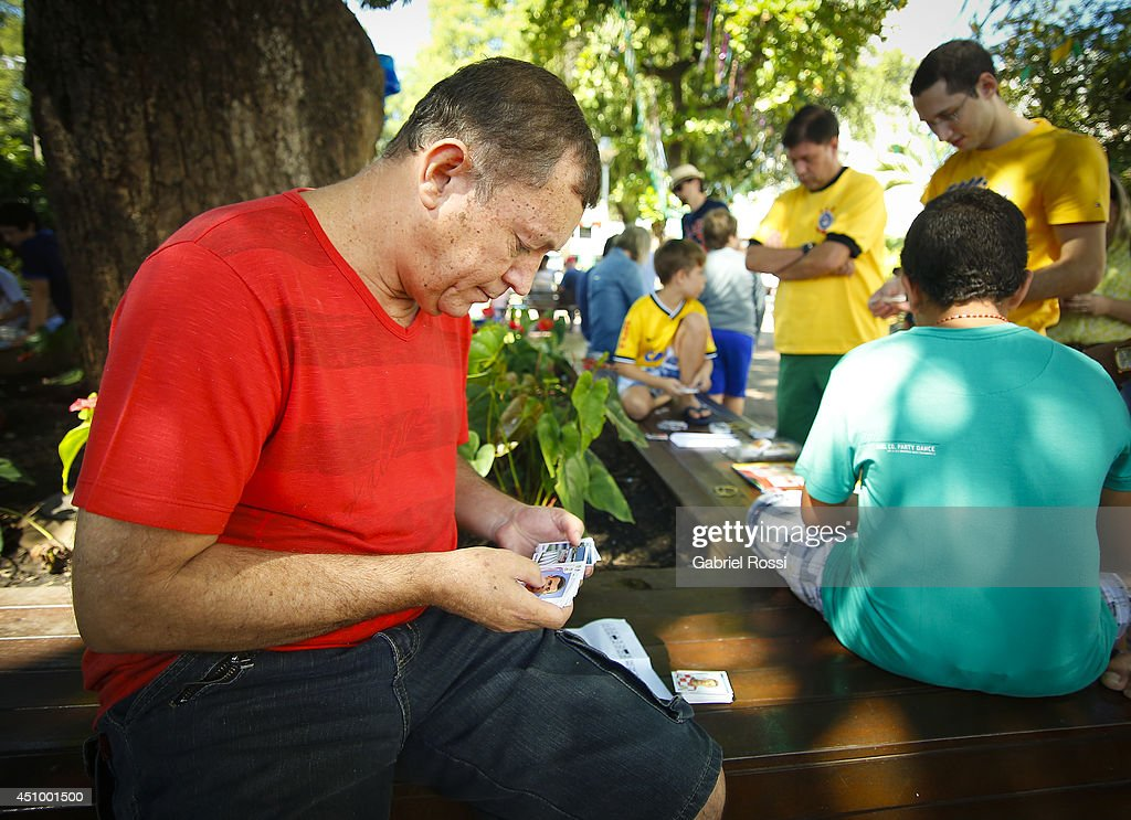 Locals gather to swap Panini 2014 FIFA World Cup Brazil stickers at Praça Popular on June 21, 2014 in Cuiaba, Brazil.