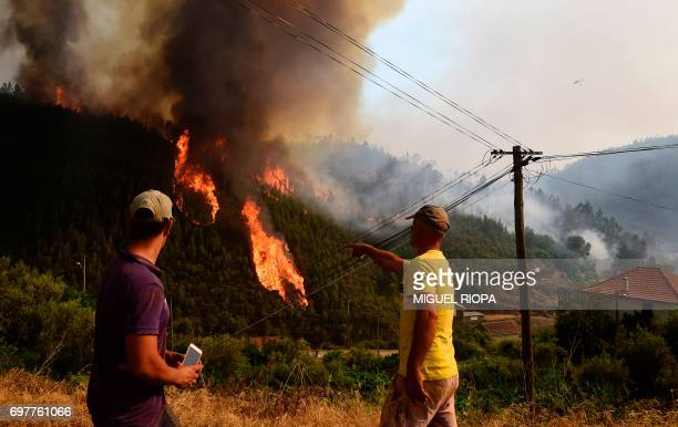 Locals gesture as they look at flames of wildfire in Carvalho next to Pampilhosa da Serra on June 19 2017 More than 1000 firefighters are still...