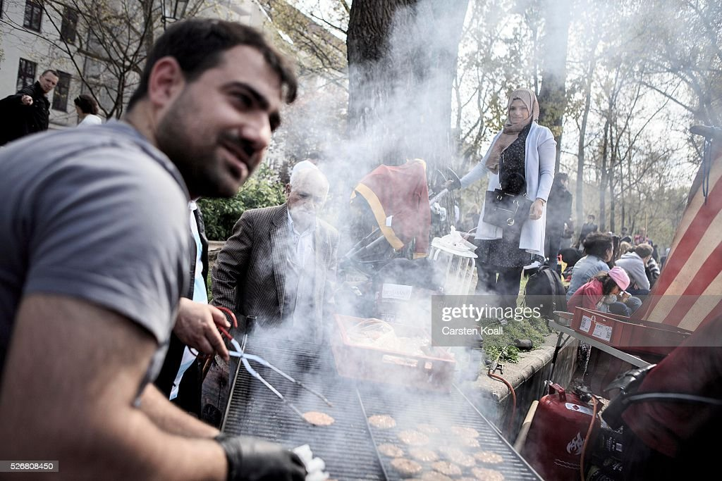 Locals grilling meat at a barbecue stand at the annual Myfest in District Kreuzberg afternoon before several demonstrations on May, 2016 in Berlin, Germany. Tens of thousands of people across Germany participated in marches and gatherings by labor unions and in some cities left-wing and anarchist activists took to the streets under heavy oversight by police. In Berlin far-right protesters also attempted to hold rallies during the day.