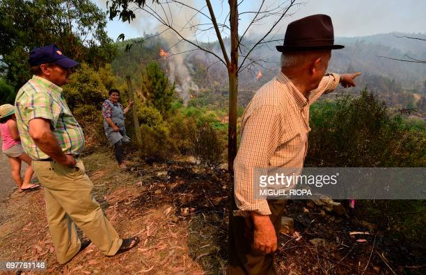 Locals look at a wildfire in Carvalho next to Pampilhosa da Serra on June 19 2017 More than 1000 firefighters are still trying to control the huge...