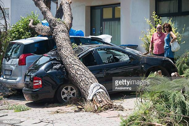 Locals look at the damage caused by last night tornado an two parked cars on July 9 2015 in Venice Italy A tornado swept through the outskirts of...