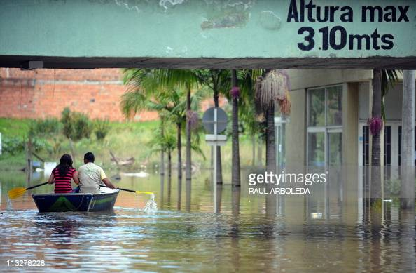Locals navigate on a canoe along a flooded street in the Rionegro municipality Antioquia department Colombia on April 29 2011 Colombia faces the...