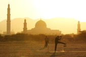 Locals play a cricket match on a dirt patch behind the Sultan Qaboos Grand Mosque on December 10 2010 in Muscat Oman The men participate in an...