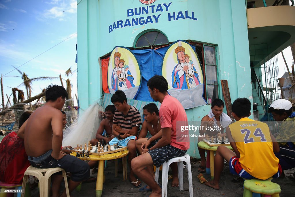 Locals play chess outside the Barangay Hall in a fishing village called Buntay on November 19, 2013 in Leyte, Philippines. Typhoon Haiyan which ripped through Philippines over a week ago has been described as one of the most powerful typhoons ever to hit land, leaving thousands dead and hundreds of thousands homeless. Countries all over the world have pledged relief aid to help support those affected by the typhoon however damage to the airport and roads have made moving the aid into the most affected areas very difficult. With dead bodies left out in the open air and very limited food, water and shelter, health concerns are growing.