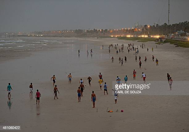 Locals play football in the rain on the beach in Maceio the base training camp for the Ghana national football team on June 22 2014 during the FIFA...