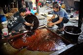Locals puts Molten Raw boiled molasses to make cooler to prepare molasses Chaku on 06 January 2015 at Tokha Kathmandu Nepal for the celebration of...