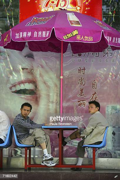 Locals sit outside a new supermarket in the new part of Lhasa city on August 6 2006 in Lhasa of Tibet Autonomous Region China Lhasa's face is ever...