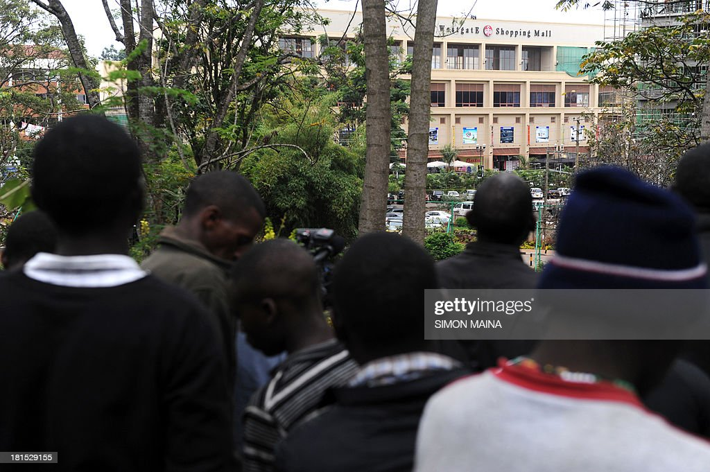 Locals stand at a distance on September 22 2013 outside the Westgate mall in Nairobi Kenyan troops were locked in a fierce firefight with Somali...