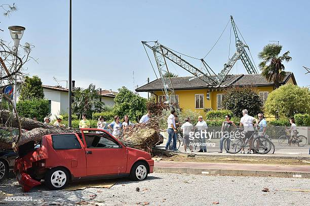 Locals standing between a fallen crane and a damaged car talk about the destruction caused by last night tornado on July 9 2015 in Venice Italy A...