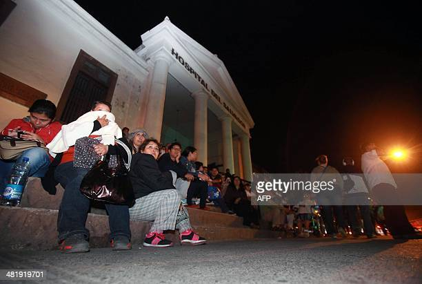 Locals take refuge on the street following a tsunami alert after a powerful 82magnitude earthquake hit off Chile's Pacific coast on April 1 2014 in...