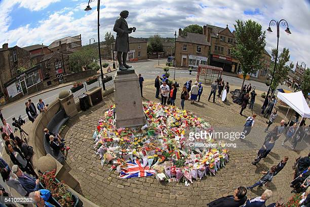 Locals view the growing amount of flowers and tributes to Jo Cox MP in Market Squre on June 18 2016 in Birstall United Kingdom The Labour MP for...