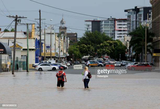 ROCKHAMPTON QLD Locals wade through floodwaters in Rockhampton Queensland after the Fitzroy River burst its banks in the aftermath of Tropical...