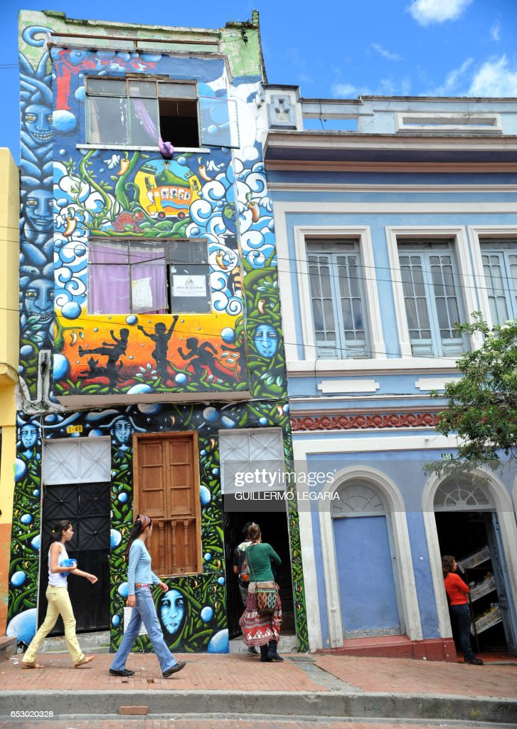 Locals walk by a painted house in Bogota, Colombia, on July 9, 2010. AFP PHOTO/Guillermo LEGARIA /
