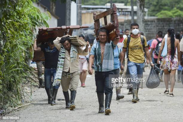 Locals walk carrying recovered belongings following mudslides caused by heavy rains in Mocoa Putumayo department southern Colombia on April 2 2017...