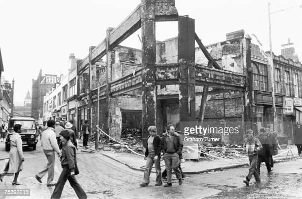 Locals walk past a building destroyed during the second night of rioting in Brixton 13th April 1981