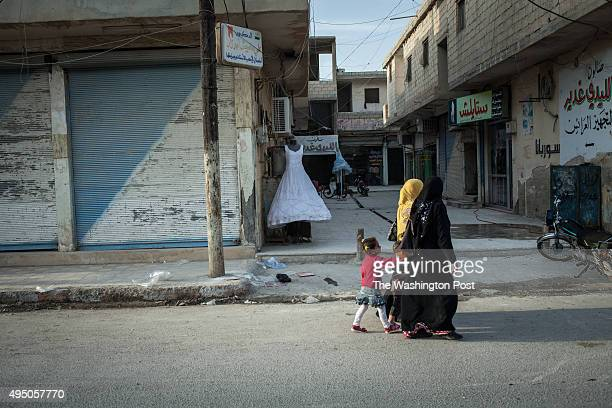 Locals walk past shuttered shops and a wedding gown on display in Tel Abyad Syria