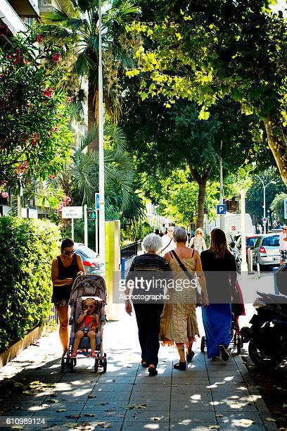 Locals walking along a tree lined avenue in Nice, France