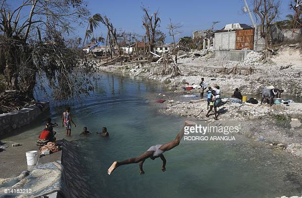 TOPSHOT Locals wash clothes in Port Salut southwest of PortauPrince on October 12 following the passage of Hurricane Matthew A week after Matthew...