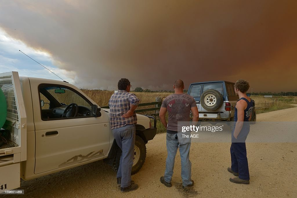 Locals watch for embers near their property as fires burn in the large rural region of Gippsland January 18, 2013 near Cowwarr, Victoria, Australia. Record heat was making conditions ripe for wildfires throughout Australia. Australia's largest city Sydney today posted its highest recorded temperature ever at 114 degrees Fahrenheit.