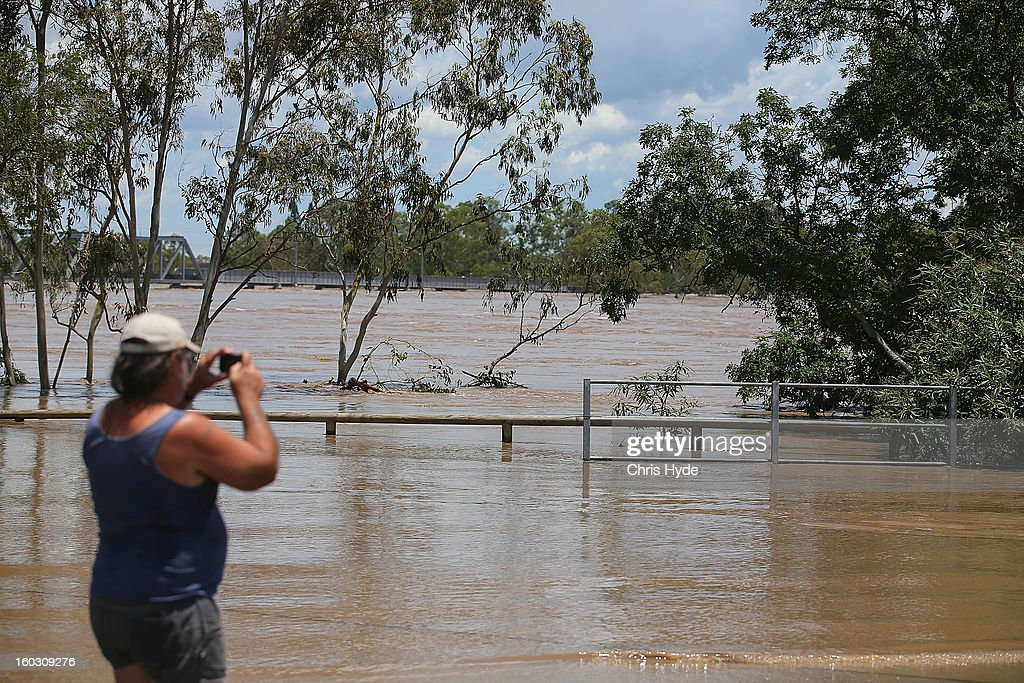 Locals watch the Burnett River rises as parts of southern Queensland experiences record flooding in the wake of Tropical Cyclone Oswald on January 29, 2013 in Bundaberg, Australia.Four deaths have been confirmed and thousands have been evacuated in Bundaberg as the city faces it's worst flood disaster in history. Rescue and evacuation missions continue today as emergency services prepare to move patients from Bundaberg Hospital to Brisbane amid fears the hospital could lose power.