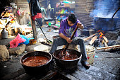 Locals whipping Molten Raw boiled molasses to make cooler to prepare molasses Chaku on 06 January 2015 at Tokha Kathmandu Nepal for the celebration...