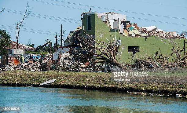 Locals work near a house destroyed by last night tornado on July 9 2015 in Venice Italy A tornado swept through the outskirts of Venice touching the...