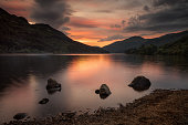 Three stones on quiet Loch Eck in sunset light, Scotland