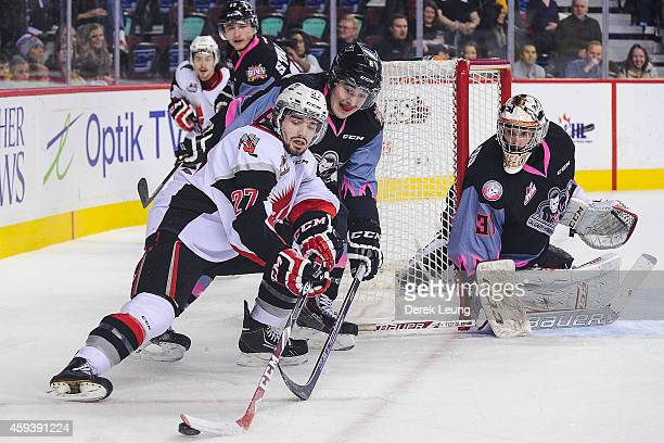 Loch Morrison of the Calgary Hitmen tries to check Torrin White of the Moose Jaw Warriors during a WHL game at Scotiabank Saddledome on November 21...