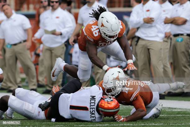 J Locke III of the Texas Longhorns tackles Jalen McCleskey of the Oklahoma State Cowboys in the second quarter at Darrell K RoyalTexas Memorial...
