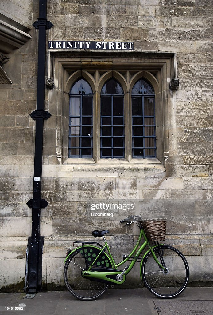 A locked bicycle leans against the wall of a building on Trinity Street in Cambridge, U.K., on Friday, March 22, 2013. In 2011, the U.K.'s government unveiled a plan to reduce state spending on higher education and shift more of the costs to students through tuition increases and a loan program. Photographer: Chris Ratcliffe/Bloomberg via Getty Images
