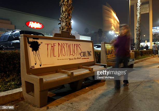A locked out Ralphs employee carries a picket sign past a bus bench left idle by a strike by the Metropolitan Transportation Authority mechanics...