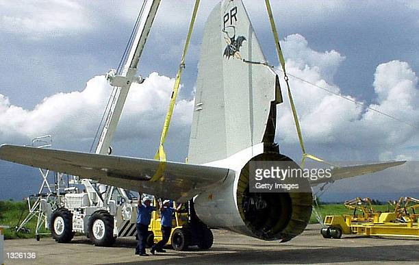 Lockheed Martin Aeronautics Co recovery team members steady the US Navy EP3E 'Aries II' tail cone following its removal from the fuselage during...