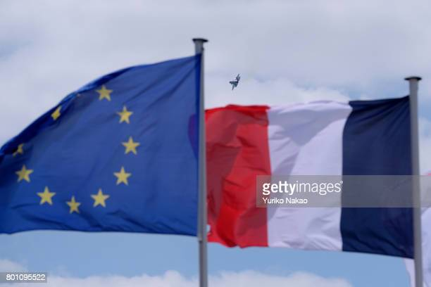Lockheed Martin F35A Lightning II performing an aerial over the Le Bourget Airport is seen past an European Union flag and a French flag on the first...