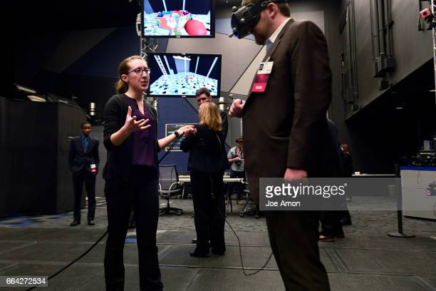 Lockheed Martin's space systems Collaborative Human Immersive Laboratory simulation engineer Arika Armstrong helping visitors adjust to virtual...