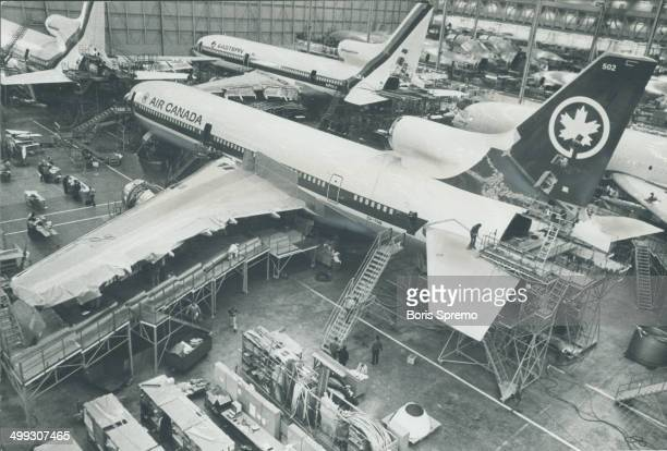 Lockheed Tristar wearing Air Canada's colors is surrounded by scaffolding as workmen complete some of the final stages in a huge assembly hangar at...