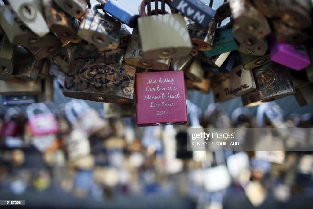 Locks attached by lovers are pictured on the railing of the Solferino bridge on October 27, 2012 in Paris, France. AFP PHOTO KENZO TRIBOUILLARD
