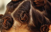 Locks of hair twisted up and secured by hairpins, close-up